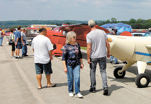 Visitors mill around planes lined up on the runway during Saturday's Wings and Wheels show at New Castle Airport. The seventh annual event featured not only planes, but also classic cars, helicopter rides and a corn roast. — Sam Luptak Jr.