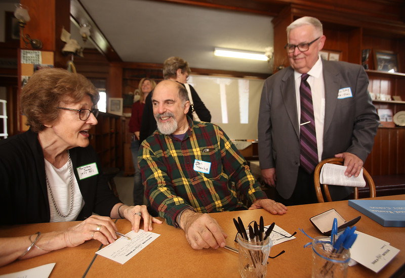 Winslow School reunion in Tyngsboro. From left, Marielena (Jacoppi) Cotter '57 of Tyngsboro, and Dean Trearchis '66 of Dracut, filling out memory cards, and Bill Day '66 of Nashua, in Littlefield Library. (SUN/Julia Malakie)