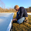 Cliff McMullan of Lancaster, a member of the Thayer Field Campus committee, works on securing a plastic lining on the ice skating rink on January 17, 2014.<br /> SENTINEL & ENTERPRISE / BRETT CRAWFORD