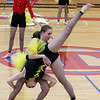 Sophomore Grace O'Connell, center, and senior Kitty Lovell do a combination cartwheel as Westford Academy winter guard competes as Tewksbury Memorial High School hosts the New England Scholastic Band Association's competition. (SUN/Julia Malakie)