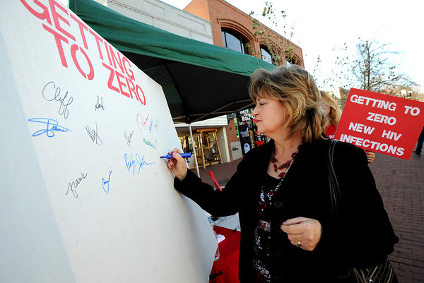 "Cossette Roberts signs the ""Getting to Zero"" Boulder set up by BCAP on the Pearl Street Mall on Friday.<br /> The Boulder County AIDS Project (BCAP) has planned an entire weekend of activities to commemorate the event, including an HIV Awareness Campaign on Pearl Street to speak with passers-by about HIV prevention, World AIDS Day, and the reality that AIDS is not over. BCAP will then welcome the Resonance Women's Chorus and the Denver Gay Men's Chorus, directed by Mark Stamper, who will present a World AIDS Day Concert from 2:00 – 3:30 pm at the First Methodist Church on Sunday.  BCAP volunteers will be supporting KBCO's Studio C CD sales, and several restaurants are participating with benefit days as well.  The full schedule can be found at  <a href=""http://www.bcap.org"">http://www.bcap.org</a>.<br /> For a video and more photos, go to  <a href=""http://www.dailycamera.com"">http://www.dailycamera.com</a>.<br /> Cliff Grassmick  / November 30, 2012"