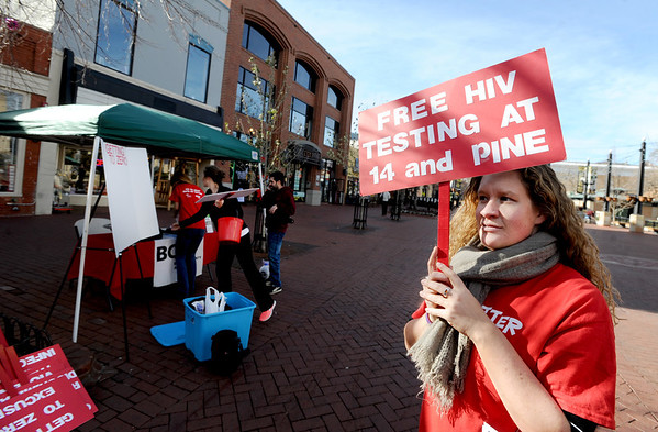 "Sarah Wilson, right, walks the Pearl Street Mall handing out ribbons and telling people about AIDS testing going on on Friday.<br /> The Boulder County AIDS Project (BCAP) has planned an entire weekend of activities to commemorate the event, including an HIV Awareness Campaign on Pearl Street to speak with passers-by about HIV prevention, World AIDS Day, and the reality that AIDS is not over. BCAP will then welcome the Resonance Women's Chorus and the Denver Gay Men's Chorus, directed by Mark Stamper, who will present a World AIDS Day Concert from 2:00 – 3:30 pm at the First Methodist Church on Sunday.  BCAP volunteers will be supporting KBCO's Studio C CD sales, and several restaurants are participating with benefit days as well.  The full schedule can be found at  <a href=""http://www.bcap.org"">http://www.bcap.org</a>.<br /> For a video and more photos, go to  <a href=""http://www.dailycamera.com"">http://www.dailycamera.com</a>.<br /> Cliff Grassmick  / November 30, 2012"