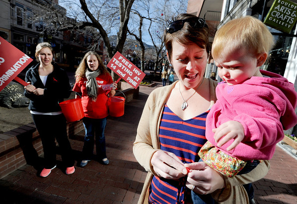 "Sarah Shea, left, and Sarah Wilson, walk the Pearl Street Mall handing out ribbons and telling people about AIDS testing going on on Friday.<br /> Rachel Veretto, and her child, Scout, take a ribbon.<br /> The Boulder County AIDS Project (BCAP) has planned an entire weekend of activities to commemorate the event, including an HIV Awareness Campaign on Pearl Street to speak with passers-by about HIV prevention, World AIDS Day, and the reality that AIDS is not over. BCAP will then welcome the Resonance Women's Chorus and the Denver Gay Men's Chorus, directed by Mark Stamper, who will present a World AIDS Day Concert from 2:00 – 3:30 pm at the First Methodist Church on Sunday.  BCAP volunteers will be supporting KBCO's Studio C CD sales, and several restaurants are participating with benefit days as well.  The full schedule can be found at  <a href=""http://www.bcap.org"">http://www.bcap.org</a>.<br /> For a video and more photos, go to  <a href=""http://www.dailycamera.com"">http://www.dailycamera.com</a>.<br /> Cliff Grassmick  / November 30, 2012"
