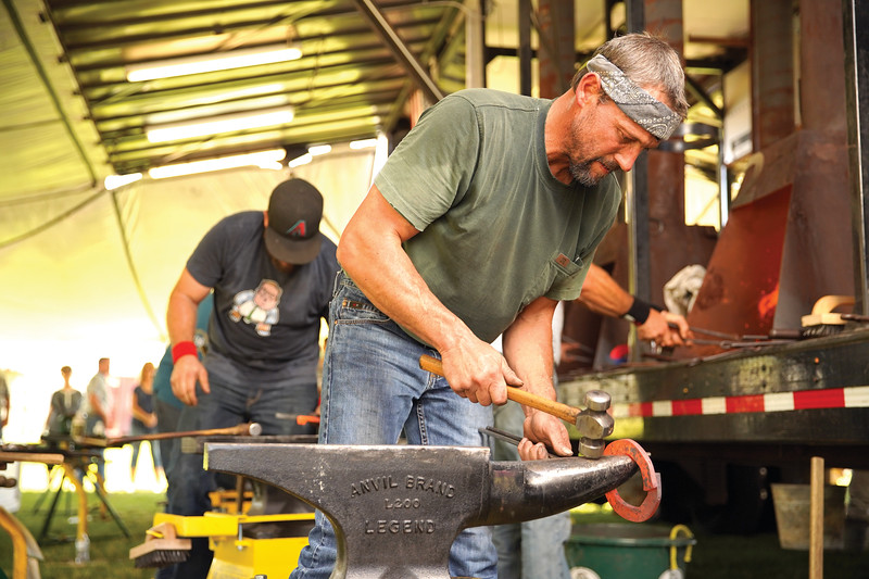 Matthew Gaston | The Sheridan Press<br>Blacksmith Travis Swenson taps the hammer on his anvil between strikes during the World Championship Blacksmiths competition Saturday, Aug. 31, 2019.