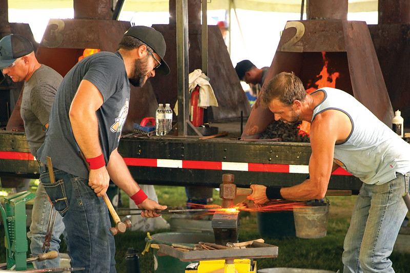 Matthew Gaston | The Sheridan Press<br>Tyson Clark, left, holds a molten hot horseshoe steady while Robert Jukes pounds the edge flat with a sledge hammer during the World Championship Blacksmiths competition Saturday, Aug. 31, 2019.