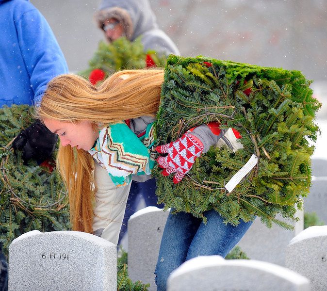 Narragansett High School junior Dakota Sorrelle, 16, of Templeton places a wreath at a headstone in the Massachusetts Veterans' Memorial Cemetery in Winchendon as part of the Wreaths Across America program, Friday morning.<br /> SENTINEL & ENTERPRISE / BRETT CRAWFORD