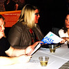 Debbie Blank | The Herald-Tribune<br /> Y assistant child care director Debbie Freyer (from left), child care director Karen Moore and senior director of member engagement Tara Britton check out the annual report and evening's program.