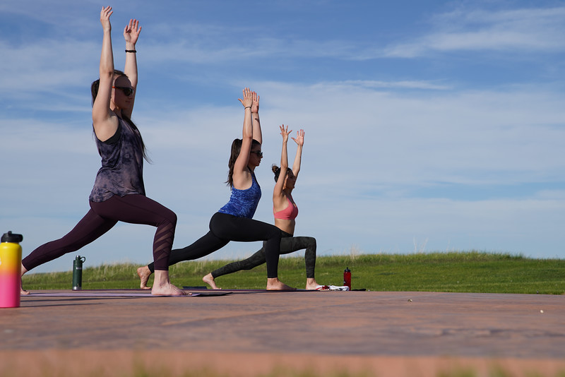 Matthew Gaston | The Sheridan Press<br>Yoga practitioners, from left, Cassie Jaeb, Monica Riesch and Lauren Nieves reach towards the heavens in the warrior 1 pose during Yoga at The Brinton hosted by Kula Space Tuesday, May 19, 2020.