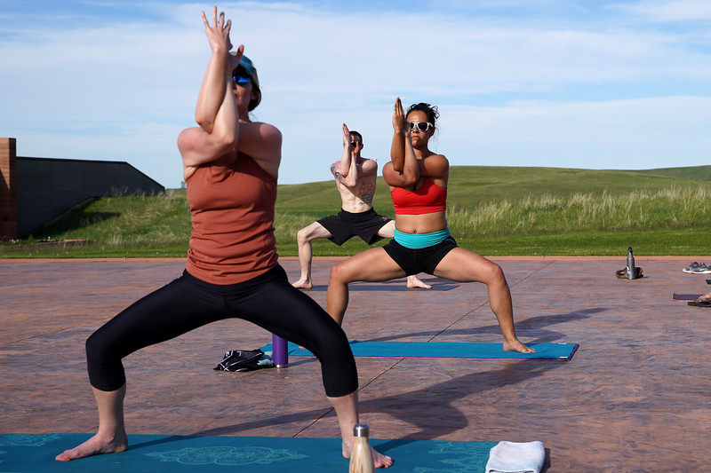 Matthew Gaston | The Sheridan Press<br>Yoga practitioners, from front to back, Kelli Johnson, Valery Notaro and Eric Zappa fall into perfect sync during the yoga flow at Kula Space's Yoga at The Brinton Tuesday, May 19, 2020.