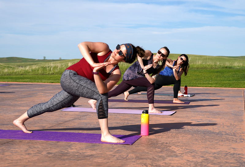 Matthew Gaston | The Sheridan Press<br>From left, Tressa Lawrence, Cassie Jaeb and Monica Riesch contort into the crescent lung twist pose during Yoga at The Brinton Tuesday, May 19, 2020. Yoga at The Brinton is so cool you got to wear shades.