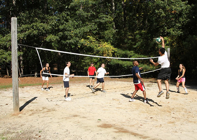 Danny Huynh of the Holy Vietnamese Church, Norcross, leaps to spike the ball over the opposing team during a game of volleyball. Young adults enjoyed some free time during an Oct. 15 retreat at Simpsonwood Conference Center, Norcross.