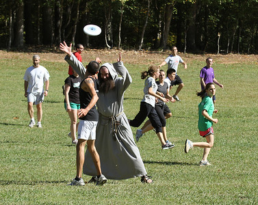 A retreatant flips a pass to a teammate as Franciscan Friars of the Renewal Father Luke Fletcher applies some defense during a game of ultimate Frisbee. Young adults enjoyed some free time between prayer, group discussions and eucharistic adoration during an Oct. 15 retreat at Simpsonwood Conference Center, Norcross.