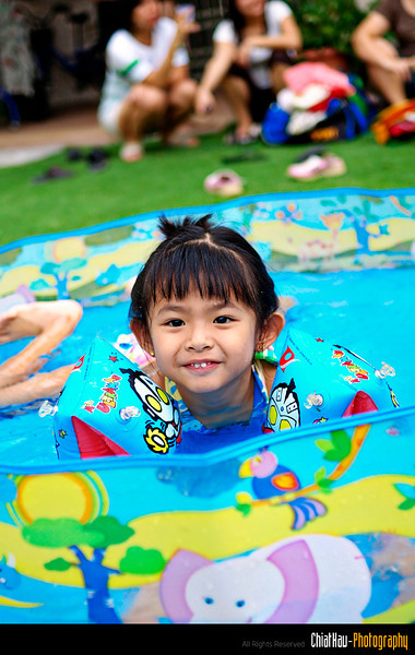 on the other side of the small pool, a cute little girl is enjoying herself...