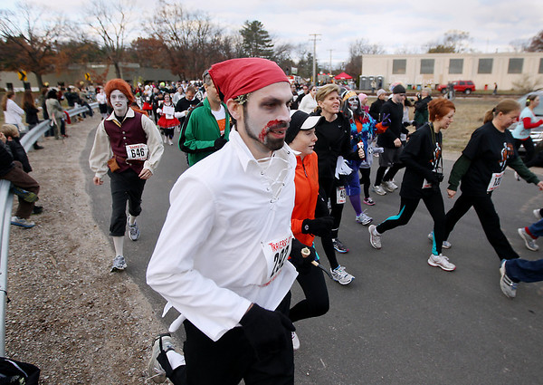 Record-Eagle/Keith King<br /> Joel Kerbleski, center, of Midland, and Julian Vandenberg, left, of Traverse City, run with others Saturday, October 27, 2012 at the start of the fourth annual Zombie Run 5k in Traverse City with proceeds from the run/walk going toward TART Trails.