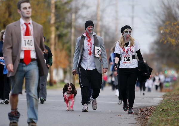 Record-Eagle/Keith King<br /> Kris and Brittney Filion, of Traverse City, walk their dog, Coffee, as they near the finish line Saturday, October 27, 2012 during the fourth annual Zombie Run 5k in Traverse City with proceeds from the run/walk going toward TART Trails.