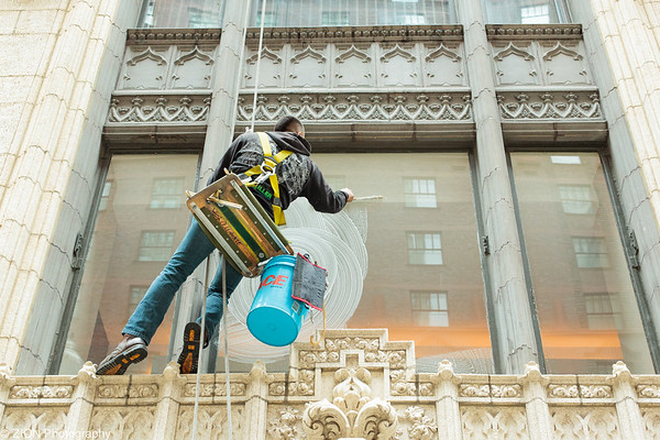 A man works to wash windows suspended by ropes