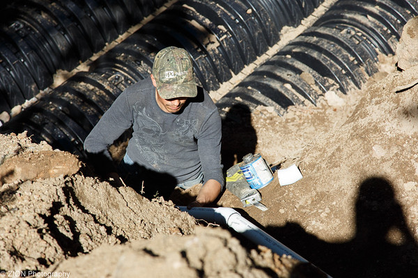 A man fits PVC pipe together while installing leachfield