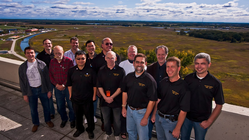 Giulio Stancari, Jim Walton Dan Bollinger, Xiaolong Zhang, CY Tan, Todd Johnson, Bruce Hanna, TS Meyer, Ron Moore, Mike Syphers, Gerry Annala, Dean Still and Alex Valeshev atop Fermilab's Wilson hall with the Tevatron accelerator ring spreading out behind them.
