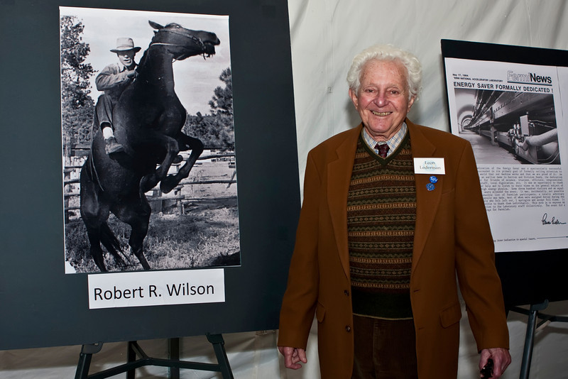 Leon Lederman, Fermilab's second director, poses next to a photo of Robert Wilson, Fermilab's first director prior to the termination of the Tevatron collider run.