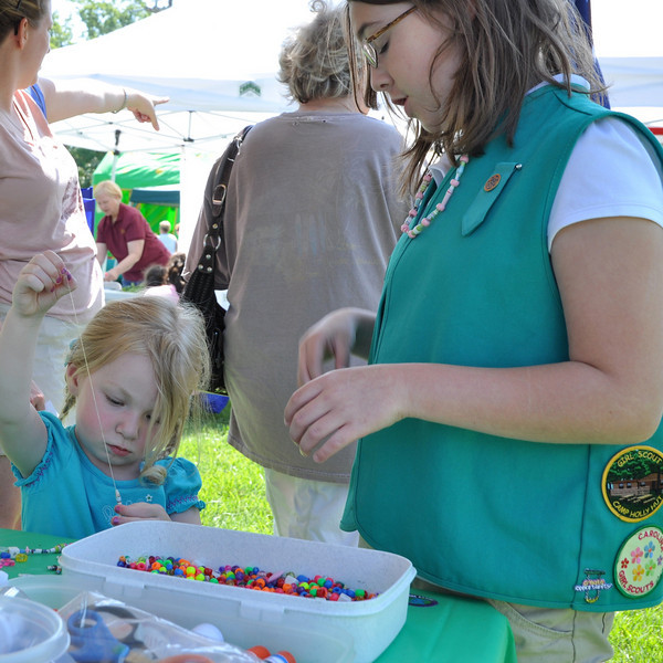 Cailyn Plummer, 10, from IT Girl Scout troop 94 helps Juliana Joyce, 3, of Monroe beading colorful necklaces.