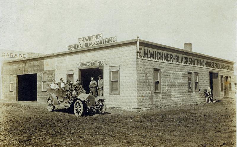 1903 Emil Henry Wichner's Blacksmith Shop_2.jpg<br /> <br /> Uncle Heinie behind wheel