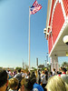 The crowd and staff sand the National Anthem as the flag rose