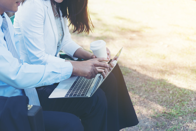 Picture of stylish mature businessman and businesswomen  sitting on a park bench with his digital tablet. Businessman and women having work discussion in the park. Man and women having free time in the park.