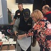 Lynne Saffie, of Somebody Cares New England, helps Luther Bryan gather items of clothing during the group's Christmas Day celebration at Community Christian Academy in Lowell. SUN / RICK SOBEY