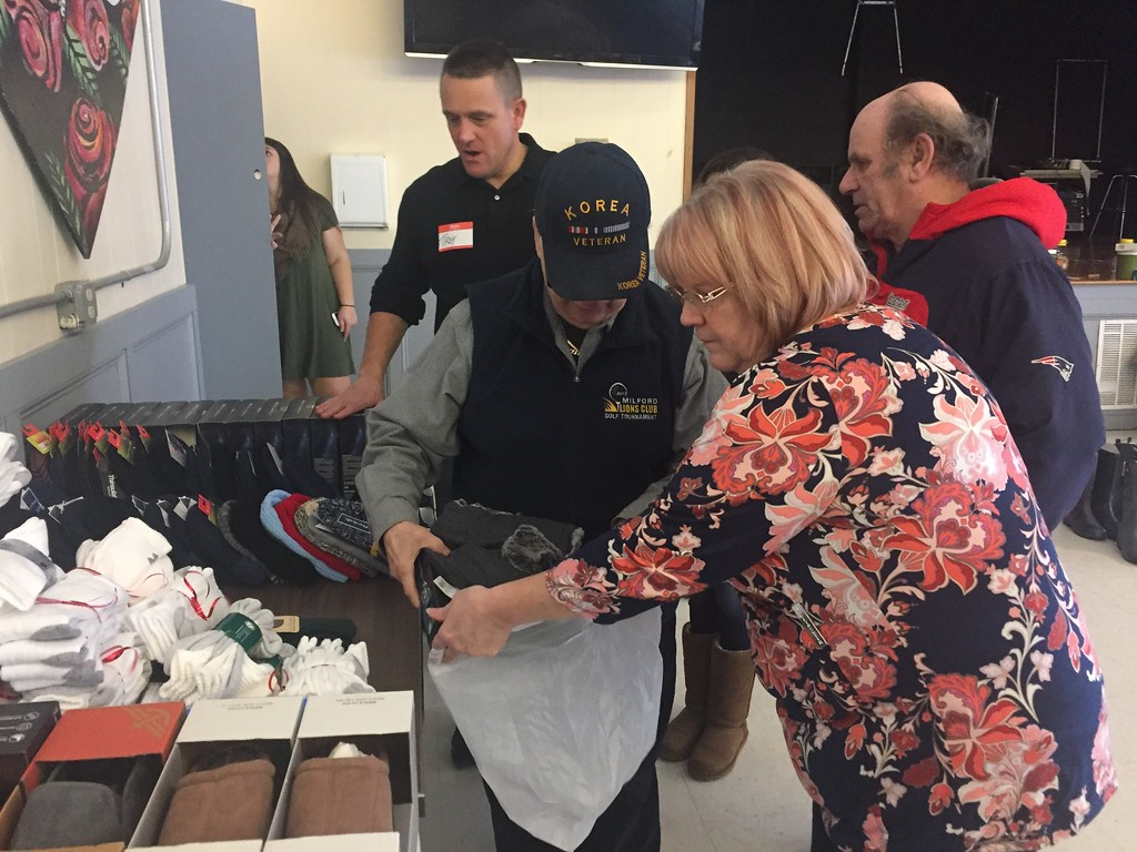 . Lynne Saffie, of Somebody Cares New England, helps Luther Bryan gather items of clothing during the group�s Christmas Day celebration at Community Christian Academy in Lowell. SUN / RICK SOBEY