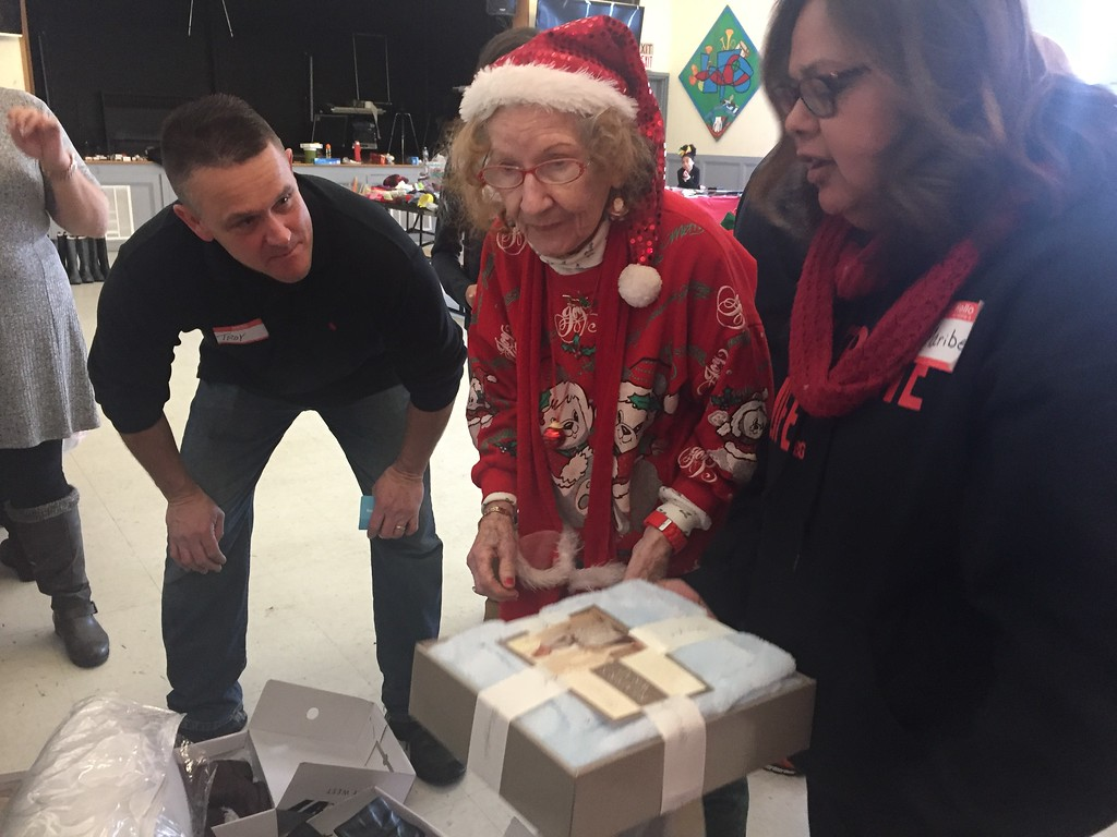 . Troy Opland, left, and Maribel Jones, right, help Eileen Lynch pick out some items as Somebody Cares New England distributes gifts at Community Christian Academy in Lowell on Christmas. SUN / RICK SOBEY