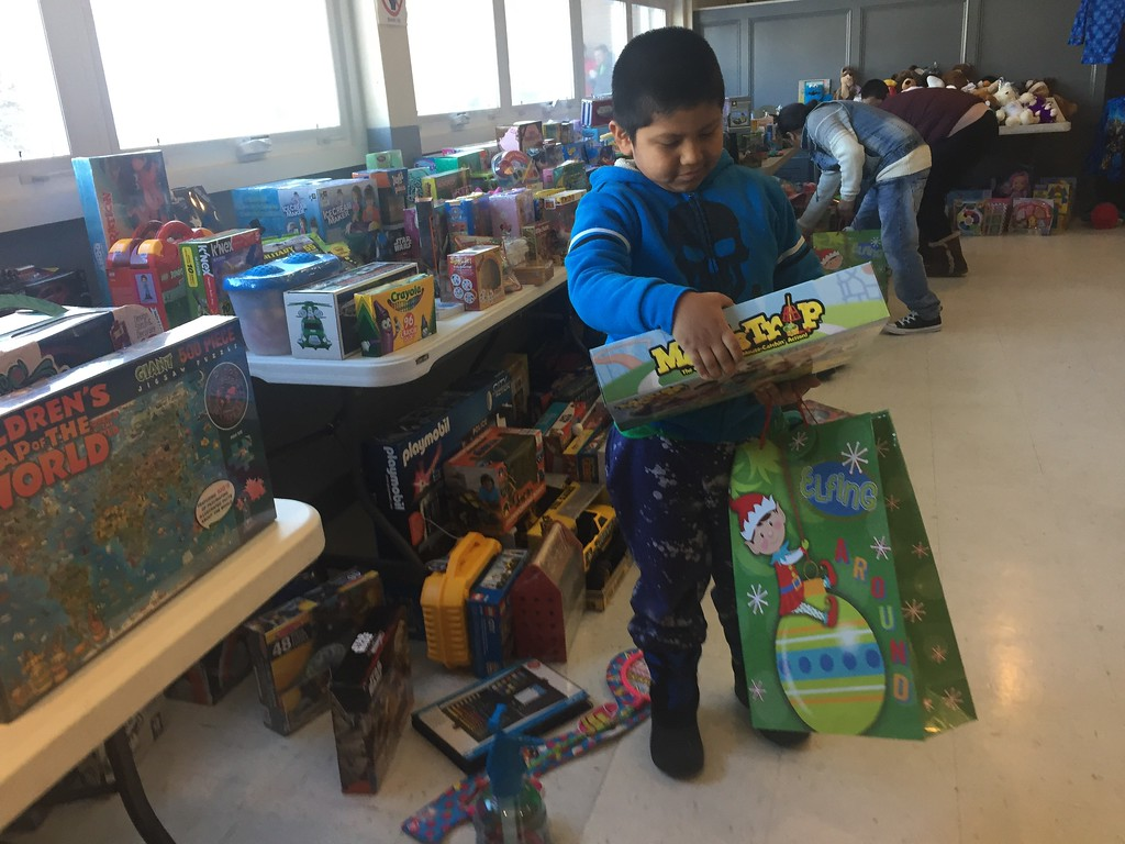 . Francisco Romero, 6, selects a game from the assortment of gifts. SUN/ RICK SOBEY