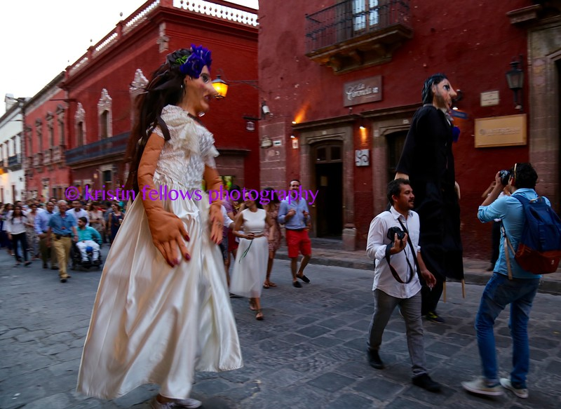 led by the photographers and puppets, the bride & groom's friends and family dance their way around town