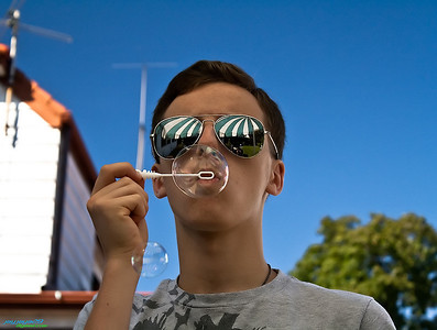 "Friend James blowing some bubbles. Sky over-colorized due to circular polarizer, given a ""matte"" feel for pleasing skin tones and texture."