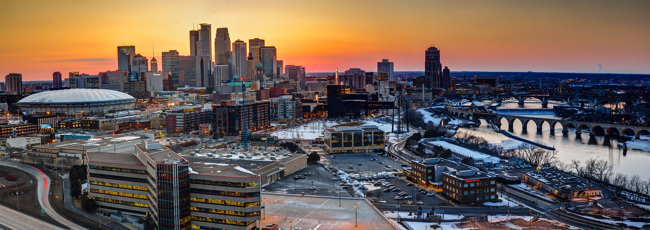 Sunset on the City - The Minneapolis skyline and riverfront just before dark as the setting sun produces a vibrant orange and yellow backdrop.  The Metrodome, downtown skyscrapers, Guthrie theater, Mill City Museum, and Stone Arch Bridge highlight this panorama.