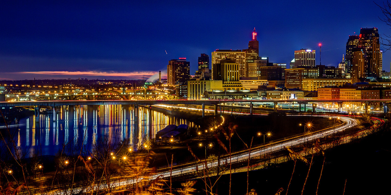 Saint Paul Night Skyline Reflections - The evening skyline of St. Paul, Minnesota is reflected in the Mississippi river as commuters make their way home in this panoramic image captured just after sunset on a summer evening.