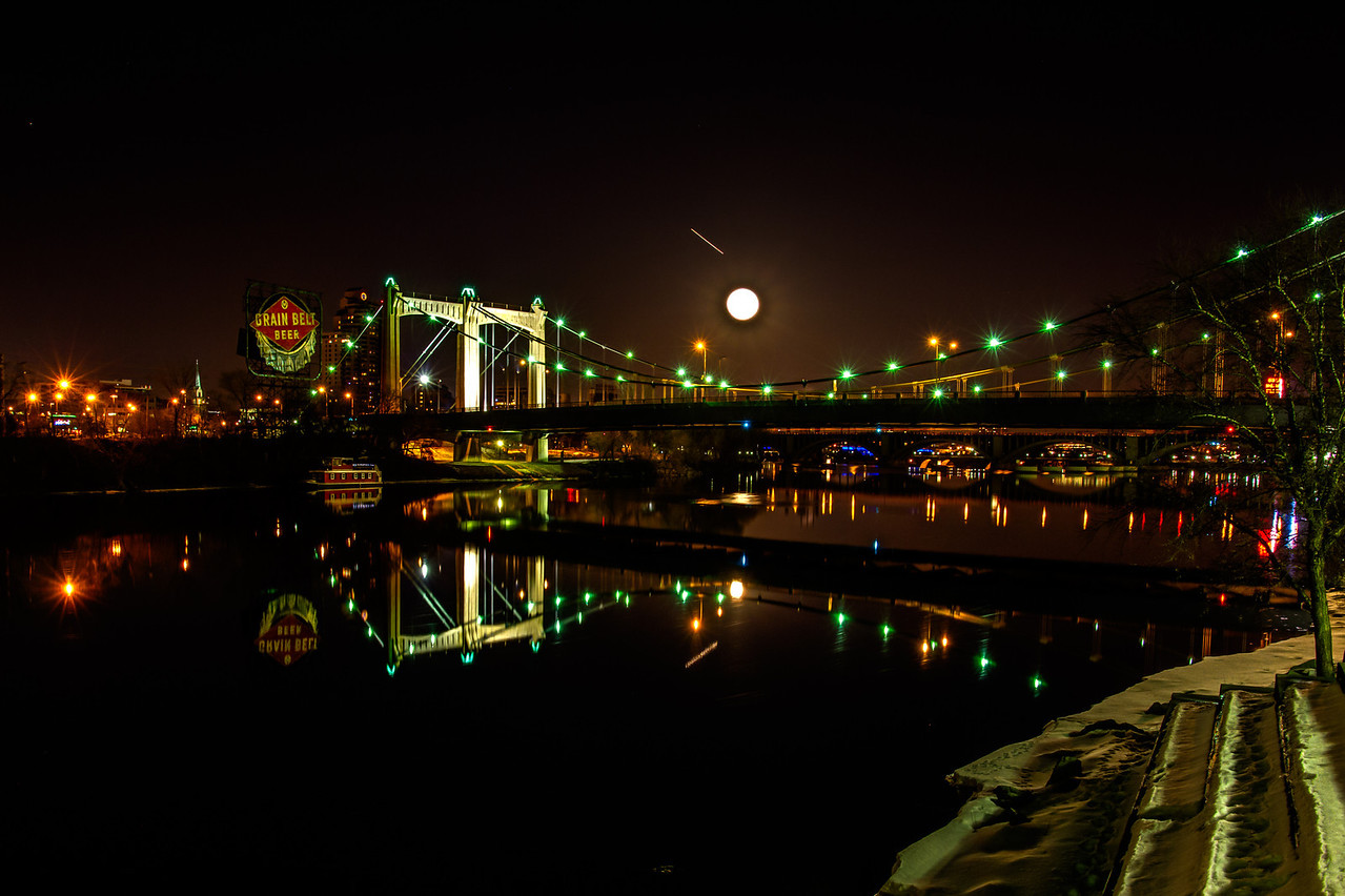 The iconic Grain Belt Beer sign and the full moon flank the reflected Hennepin Avenue Bridge over the glassy surface of the Mississippi river near downtown Minneapolis.