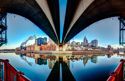 The St. Paul skyline bends away from the underside of the Wabasha Street bridge on Raspberry Island and is mirrored in the tranquil water of the mighty Mississippi at dawn.