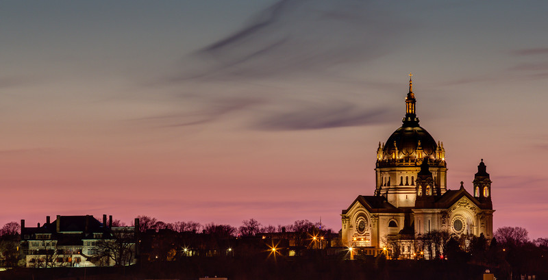 The Cathedral of Saint Paul dwarfs the James J. Hill mansion in this sunset image captured from the bluffs across the Mississippi river.