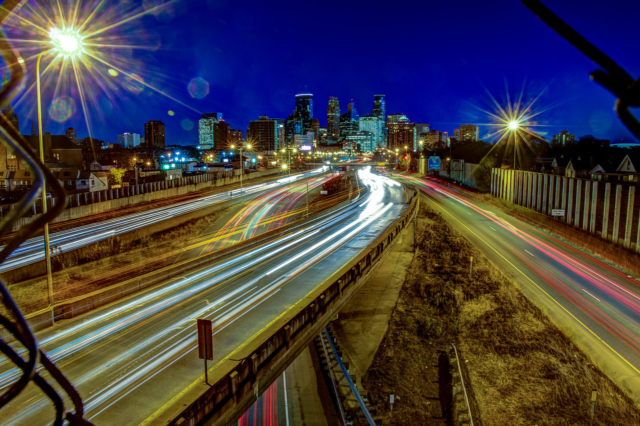 Hurrying Home - Commuting cars are reduced to mult-colored streaks of light and streetlights are starbursts in this long exposure of the downtown Minneapolis skyline captured from above the 35W freeway.