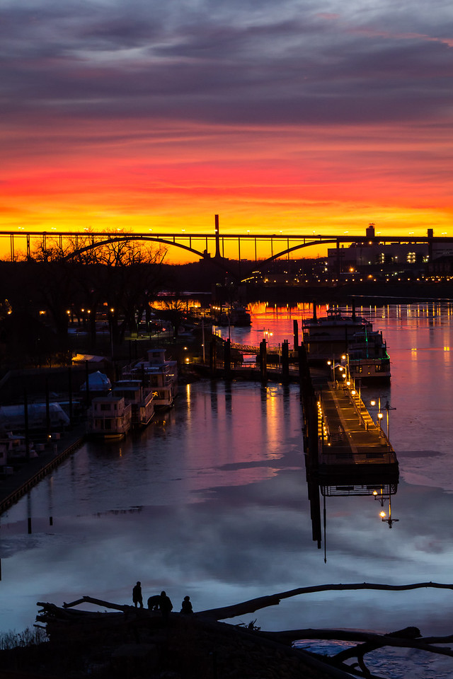 Vivid colors fill the sky and are reflected on the water on this unseasonably warm January evening in 2012.  This image was captured from Raspberry Island in the Mississippi River in downtown St. Paul as the sun was setting over the Smith Avenue High Bridge.