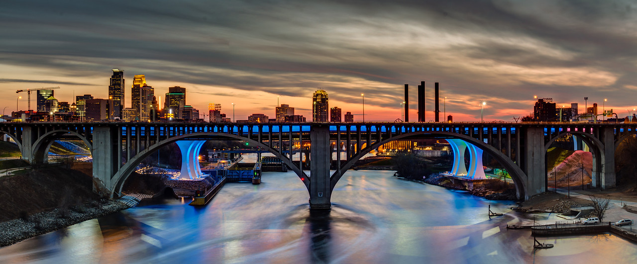 The darkening sky looms over the skyline of Minneapolis and the Mississippi river in this long exposure panorama captured at sunset.