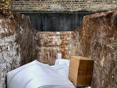 A skip with a cardboard box
