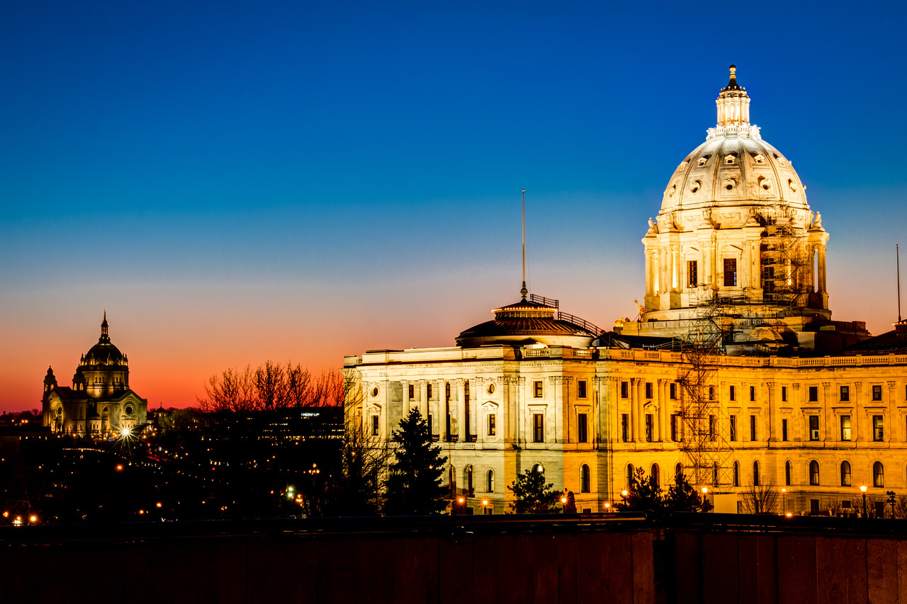 The Minnesota capitol building is about to undergo a two year renovation.  Here it's seen with the Cathedral of Saint Paul in the background before the scaffolding goes up - along with a beautiful winter sunset sky.