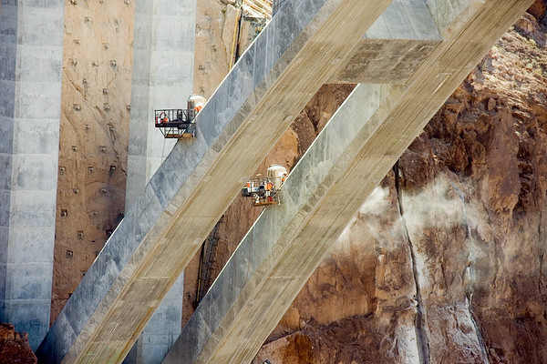 Construction workers on the Hoover Dam Bridge are perched perched precariously over the Colorado River hundreds of feet below.