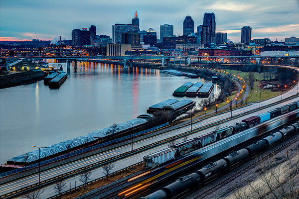 The port of St. Paul is a busy place at twilight time.   Freight trains, river barges, and commuting motorists make their way as the city lights come on.
