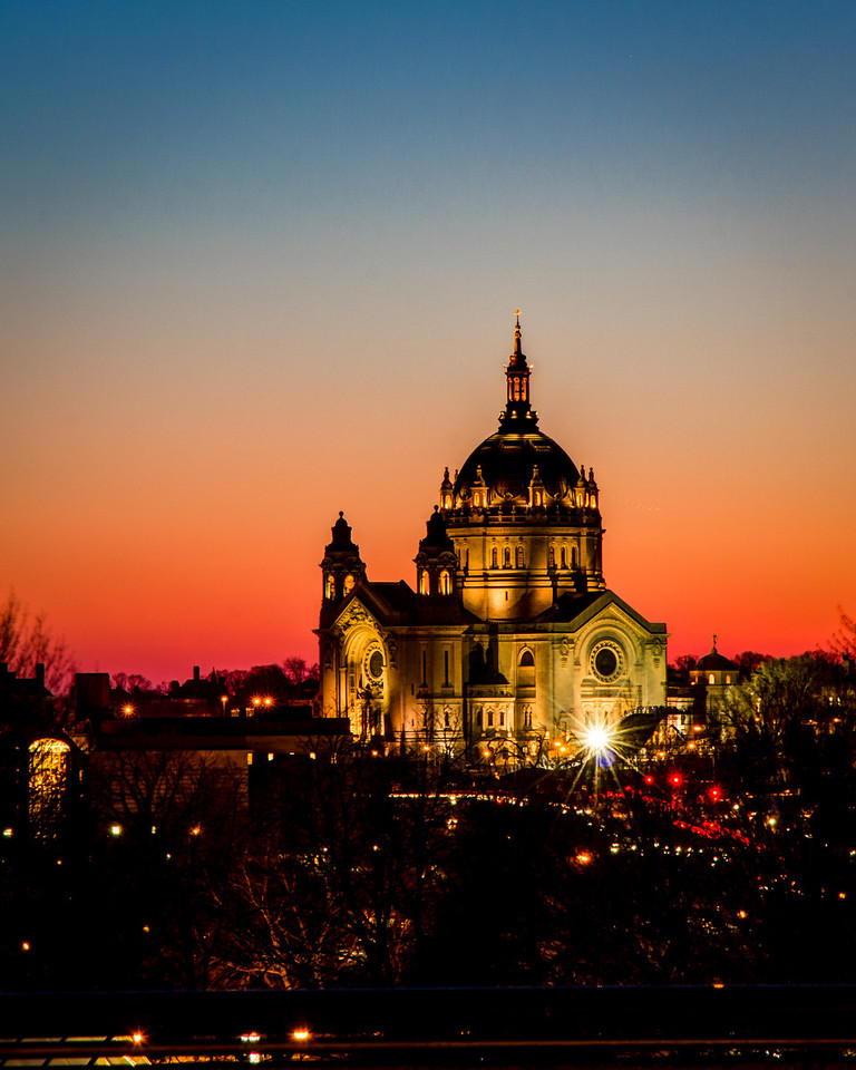 The winter sunset saturates the sky behind the Cathedral of Saint Paul, captured from the grounds of the state capitol in St. Paul, Minnesota.