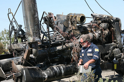 The remains of the front cab of the Semi Truck after it was ingulfed in flames.  A semi truck overturned on Hwy 101 near the Hwy 84 Woodside Exit at about 12:50pm.  No fatalities and two injuries requiring hospitalization were reported.  Pictured is the window that was broken as a result of the crash.