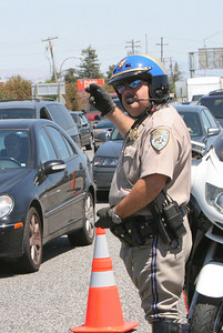 A CHP Officer directs traffic as both lanes to HWY 101 were clogged for hours.  A semi truck overturned on Hwy 101 near the Hwy 84 Woodside Exit at about 12:50pm.  No fatalities and two injuries requiring hospitalization were reported.  Pictured is the window that was broken as a result of the crash.