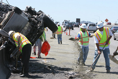 Workers clean up diesel fuel which spilled onto the highway.  A semi truck overturned on Hwy 101 near the Hwy 84 Woodside Exit at about 12:50pm.  No fatalities and two injuries requiring hospitalization were reported.  Pictured is the window that was broken as a result of the crash.