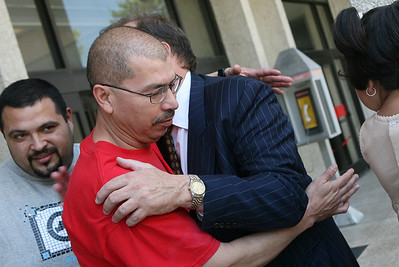 Jose Delgado, Father of the defendant Edith Delgado, recieves a congratulatory hug from defense lawyer Randy Moore in relief of the final verdict outside the courthouse in Redwood City.  Son Juan Delagdo smiles in the background.